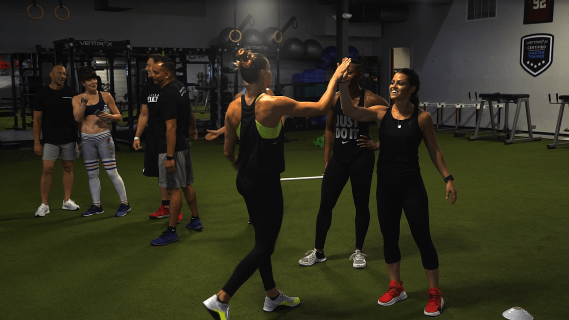 male and female athletes at a gym exercising in a group